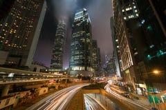 Lichter streifen vom Verkehr mit modernen Gebäuden in der Stadtnacht stockfotografie