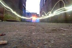 Lichter werfen eine alte Ziegelsteingasse nieder Lizenzfreie Stockbilder