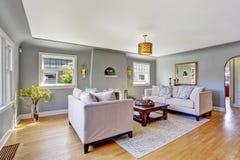 Lichtgrijze woonkamer met witte banken Royalty-vrije Stock Fotografie