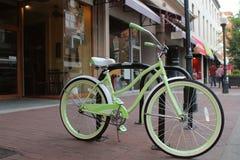 Lichtgroene fiets naast de straat op een stoep in het het winkelen district van een charmante stad stock foto's