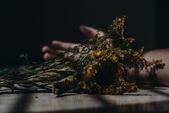 Lichtjes droge gele bloemen op een lijst in een donkere ruimte royalty-vrije stock afbeeldingen