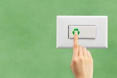 Lichtschalter auf einem grünen Wandhintergrund Stockfotografie
