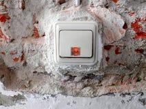 Lichtschalter in einer Wand mit entferntem Gips und sichtbaren Ziegelsteinen stockfotos