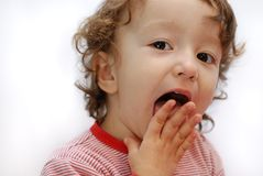 Lick. Child licking her own fingers Stock Photo