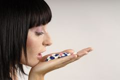 Lick it!. Young woman with colours pills Royalty Free Stock Photos