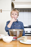 Licking batter from a bowl in a kitchen Royalty Free Stock Image