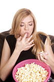Licking fingers popcorn Stock Images