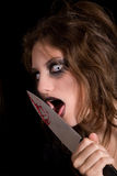 Licking the knife. Murderous woman with very scary eyes licking the blood of her knife royalty free stock image
