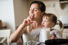 Licking of  whipping cream - mother with daughter Stock Image
