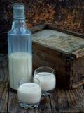 Licor Baileys de la crema del café irlandés en vidrio y botle en fondo de madera Foto de archivo