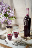 Licor caseiro da groselha com flores lilás Fundo de madeira Imagem de Stock