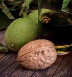 Licor de Nocino hecho con las nueces y el alcohol verdes inmaduros imagenes de archivo