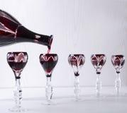 Licor vermelho de derramamento nos produtos vidreiros do vintage, jantar do bufete Conceito do aperitivo imagem de stock royalty free