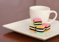Licorice allsorts on a white plate. Licorice allsorts candy on a white plate with a cup of coffee Stock Photo