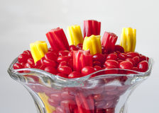Licorice in a clas jar red and yellow. Licorice and red hots in a glass Stock Photo