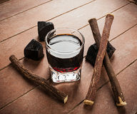 Licorice liqueur with pure blocks and roots. Stock Image