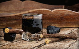 Licorice liqueur with pure blocks and roots. Royalty Free Stock Photos
