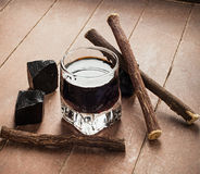 Licorice liqueur with pure blocks and roots. Licorice liqueur with pure blocks and roots on wooden table Stock Photo