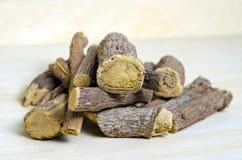Licorice or liquorice root sticks isolated on wood background Stock Photo