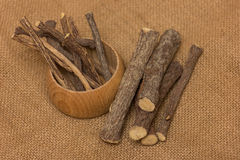 Licorice root sticks. Dried licorice root in a wooden pot on a burlap sack as a background Stock Photo