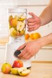 Licuadora blanca con las manzanas en una tabla de madera Foto de archivo