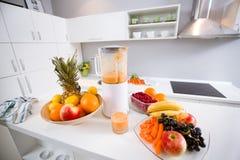 Licuadora eléctrica con las frutas y el zumo de naranja Fotos de archivo libres de regalías