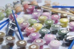 Liczący zbiorniki z farbami i muśnięciami różni rozmiary Dla malować liczbami Rozlewający out na białym tle obrazy stock