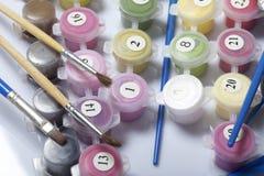 Liczący zbiorniki z farbami i muśnięciami różni rozmiary Dla malować liczbami Rozlewający out na białym tle obrazy royalty free