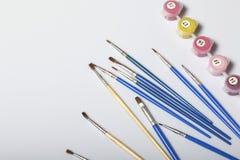 Liczący zbiorniki z farbami i muśnięciami różni rozmiary Dla malować liczbami Rozlewający out na białym tle zdjęcia stock