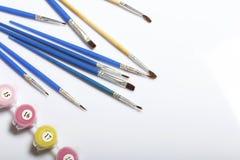 Liczący zbiorniki z farbami i muśnięciami różni rozmiary Dla malować liczbami Rozlewający out na białym tle fotografia stock