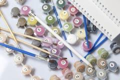 Liczący zbiorniki z farbami i muśnięciami różni rozmiary Dla rysować liczbami Notepad i ołówek dla nakreśleń Rozlewający o obraz stock