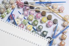 Liczący zbiorniki z farbami i muśnięciami różni rozmiary Dla rysować liczbami Notepad i ołówek dla nakreśleń Rozlewający o zdjęcie stock
