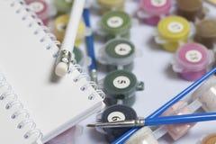 Liczący zbiorniki z farbami i muśnięciami różni rozmiary Dla rysować liczbami Notepad i ołówek dla nakreśleń Rozlewający o zdjęcia stock
