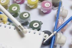 Liczący zbiorniki z farbami i muśnięciami różni rozmiary Dla rysować liczbami Notepad i ołówek dla nakreśleń Rozlewający o zdjęcie royalty free
