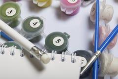 Liczący zbiorniki z farbami i muśnięciami różni rozmiary Dla rysować liczbami Notepad i ołówek dla nakreśleń Rozlewający o obrazy stock