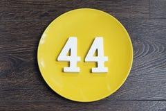 Liczba czterdzieści cztery na żółtym talerzu zdjęcia royalty free