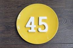 Liczba czterdzieści pięć na żółtym talerzu fotografia stock