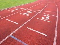 Liczba jeden i numer dwa, czerwony gumowy działający tor wyścigów konnych Zdjęcia Stock