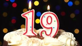 Liczba 19 na górze torta dmucha out przy końcówką - dziewiętnaście urodziny świeczki paleń - Koloru zamazany tło zbiory wideo