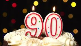Liczba 90 na górze torta dmucha out przy końcówką - dziewiećdziesiąt urodziny świeczki palenia - Koloru zamazany tło zdjęcie wideo