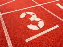Liczba trzy Bielu śladu liczba na czerwonym gumowym torze wyścigów konnych, Obraz Royalty Free