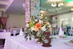 Liczba trzy i nieociosany kwiatu przygotowania z beżowymi różami przy stołem dla gości na ślubnej sala _ Fotografia Royalty Free
