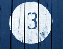 Liczba trzy na drewniany błękit tonującej ścianie Obrazy Royalty Free
