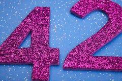 Liczby czterdzieści dwa purpury barwią nad błękitnym tłem rocznica obrazy royalty free