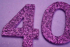 Liczby czterdzieści purpury barwią nad purpurowym tłem rocznica obrazy stock