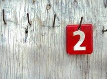 Liczby 2 na etykietkach wiesza w stary drewnianym Zdjęcia Royalty Free