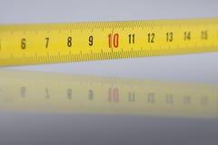 Liczby na pomiarowej taśmie 10 na ostrości - szczegóły z odbiciem - Obrazy Stock