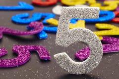 Liczby pięć srebny kolor nad barwionym tłem rocznica Zdjęcia Stock