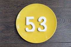 Liczebnik pięćdziesiąt trzy dwa na żółtym talerzu Zdjęcia Stock