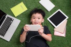 ?liczna ch?opiec s?ucha muzyka na trawie z jego laptopem, pastylk? i notatnikami woko?o, zdjęcia royalty free